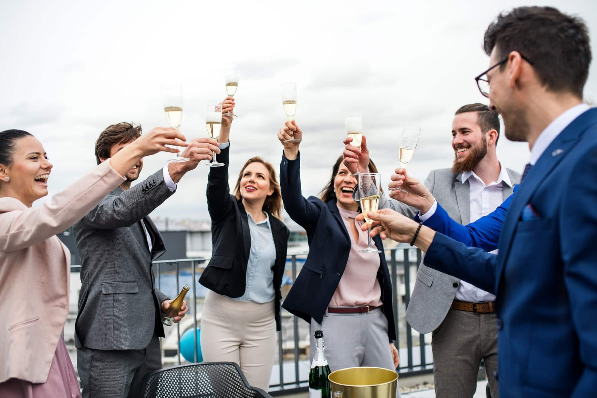 A group of joyful businesspeople having a party outdoors on roof terrace in city
